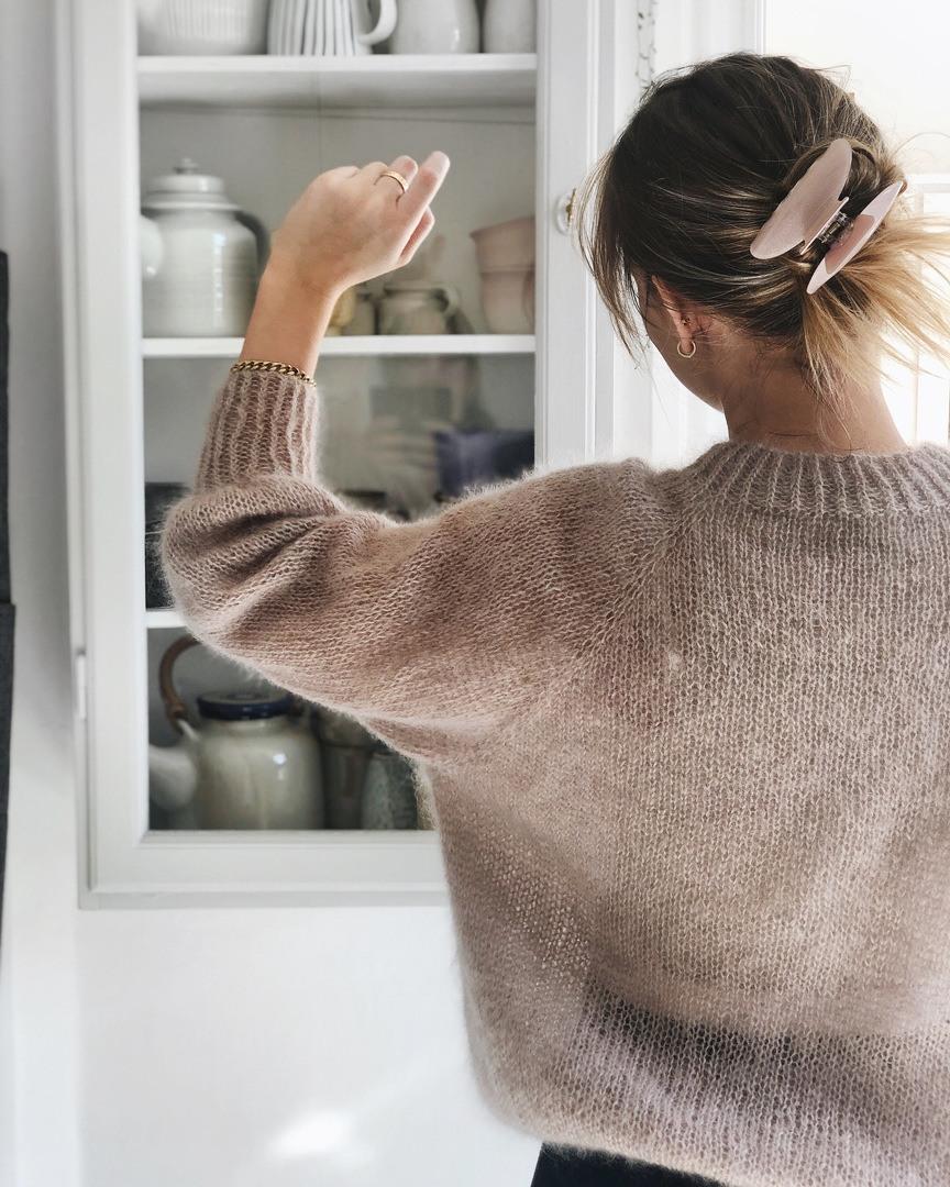 Ung kvinde i hjemmestrikket sweater